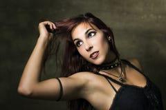 Ung kvinna med gotisk och heavy metalstil som poserar på smutsig wa Fotografering för Bildbyråer