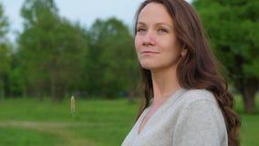 Ung kvinna med gräsbladet som ser solen arkivfilmer