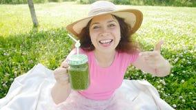 Ung kvinna med gröna grönsaksmoothies i parkera arkivfilmer