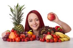 Ung kvinna med grönsaker som visar ett äpple Arkivbild