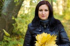 Ung kvinna med gula höstleaves Arkivfoto