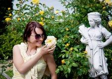 Ung kvinna med gula rosor i trädgården Arkivfoto