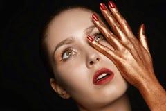 Ung kvinna med guld- händer Arkivfoto