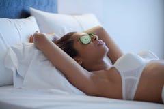 Ung kvinna med gurkaskivor i säng Arkivfoto