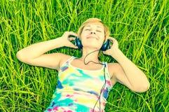 Ung kvinna med hörlurar royaltyfri bild