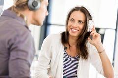Ung kvinna med hörlurar inomhus Arkivfoton