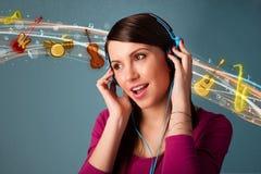 Ung kvinna med hörlurar som lyssnar till musik Royaltyfri Fotografi