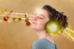 Ung kvinna med hörlurar som lyssnar till musik Arkivbilder