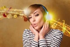 Ung kvinna med hörlurar som lyssnar till musik Arkivbild