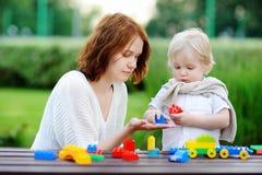 Ung kvinna med hans litet barnson som spelar med färgrika plast- kvarter Arkivbilder