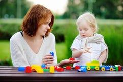 Ung kvinna med hans son som spelar med plast- kvarter Arkivfoton