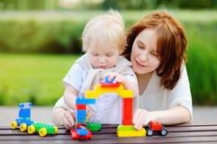 Ung kvinna med hans son som spelar med plast- kvarter Royaltyfri Fotografi