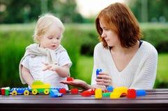 Ung kvinna med hans son som spelar med plast- kvarter Arkivbild