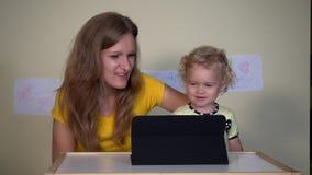 Ung kvinna med hennes barnflicka som ser roliga tecknade filmer på minnestavladatoren arkivfilmer