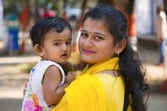 Ung kvinna med hennes dotter som ler på kameran arkivbild