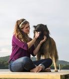 Ung kvinna med hennes hund på en skeppsdocka Royaltyfri Fotografi