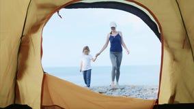 Ung kvinna med hennes lilla dotter att skriva in det campa tältet som vilar vid havet arkivfilmer