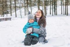 Ung kvinna med hennes lilla son som spelar i den insnöade vintern arkivfoto