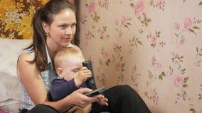 Ung kvinna med hennes son som hemma sitter på soffan med fjärrkontroll från TV:N Se skärmen uppmärksamt lager videofilmer