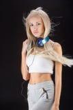 Ung kvinna med hörlurar och telefonen Royaltyfria Bilder