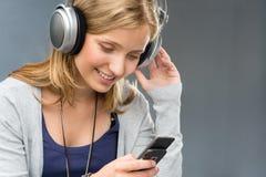 Ung kvinna med hörlurar som kontrollerar den mobila telefonen Arkivfoton