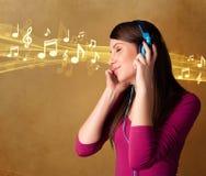 Ung kvinna med hörlurar som lyssnar till musik Arkivfoton
