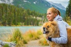 Ung kvinna med hunden i vildmark royaltyfri fotografi