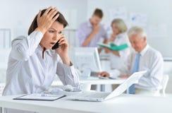 Ung kvinna med huvudvärken som arbetar i kontoret royaltyfri foto