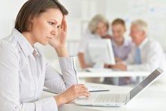 Ung kvinna med huvudvärken som arbetar i kontoret royaltyfria foton