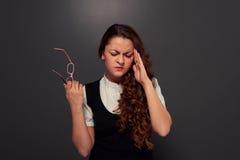 Ung kvinna med huvudvärkinnehavexponeringsglas Arkivbild