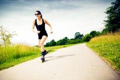 Ung kvinna med Inline skridskor Arkivfoton