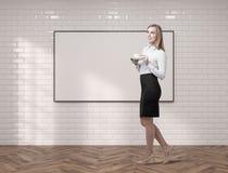 Ung kvinna med kaffe och en whiteboard Arkivbilder