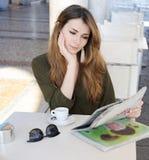 Ung kvinna med kaffe och tidningen Arkivbilder
