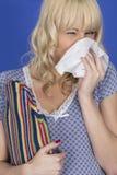 Ung kvinna med kall influensa som blåser näsan som rymmer en varmvattenflaska Arkivbilder