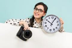 Ung kvinna med kameran och klockor Royaltyfri Foto