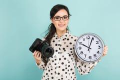 Ung kvinna med kameran och klockor Arkivbild