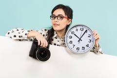 Ung kvinna med kameran och klockor Royaltyfria Bilder