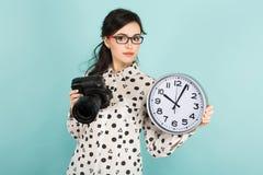 Ung kvinna med kameran och klockor Royaltyfri Bild