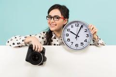 Ung kvinna med kameran och klockor Arkivfoto