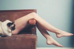 Ung kvinna med katten som kopplar av på soffan Arkivfoto