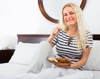 Ung kvinna med kex i säng Arkivbild