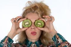 Ung kvinna med kiwifruiten Arkivbild