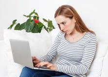 Ung kvinna med koncentration på en dator arkivfoton