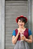 Ung kvinna med koppen av lemonad nära träväggen Royaltyfri Foto