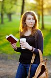 Ung kvinna med koppen kaffe och boken Arkivbild
