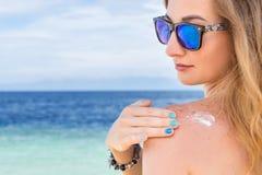 Ung kvinna med kräm för beskyddande för solglasögonapplyngsol på hennes hand på det tropiska turkoshavet för strand nästan under arkivbild