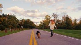 Ung kvinna med lång hårspring med hans hund på vägen i parkera arkivfilmer