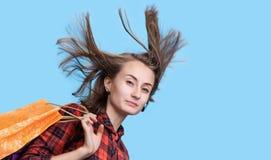 Ung kvinna med långt blåsa hår och shoping påsar Fotografering för Bildbyråer
