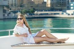 Ung kvinna med långt blont hår på yachten Arkivfoto