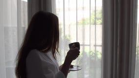 Ung kvinna med långt hår i det vita anseendet för badrockdrinkkaffe nära fönstret hemma lager videofilmer